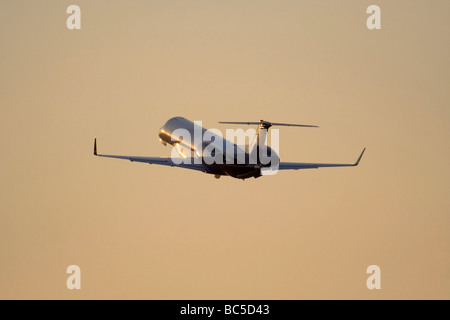 Business jet taking off at sunset. No proprietary details visible. - Stock Photo