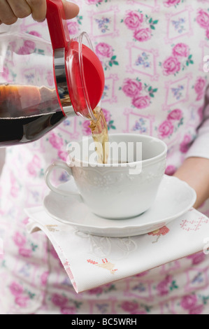 Woman pouring coffee into cup - - Stock Photo