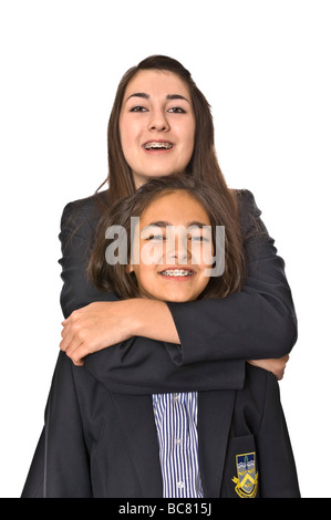 Vertical close up portrait of two teenage sisters in their school uniforms hugging each other against a white background - Stock Photo