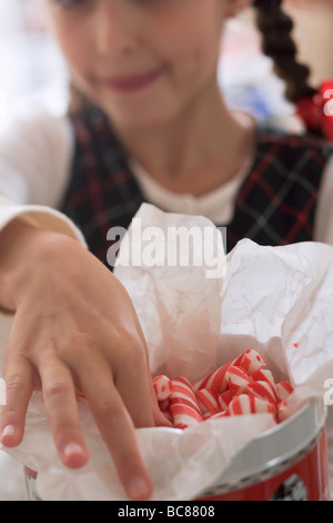 Girl reaching for candy sticks in jar - - Stock Photo