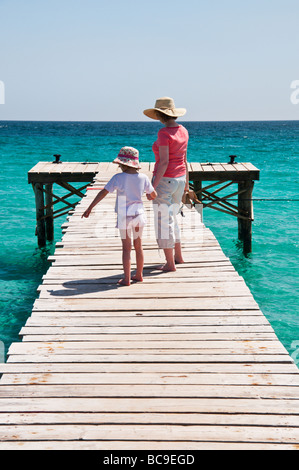 A woman and young girl on a boardwalk near C'an Picafort, Majorca, Spain. - Stock Photo
