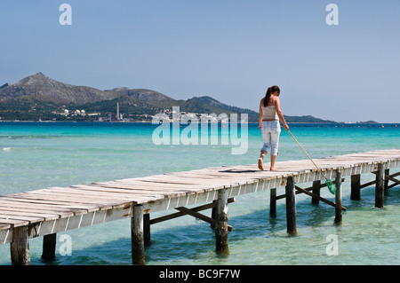 A girl with a fishing net walking on a boardwalk near Can Picafort, Majorca, Spain. - Stock Photo
