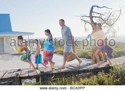 Family running on pier near swimming pool - Stock Photo