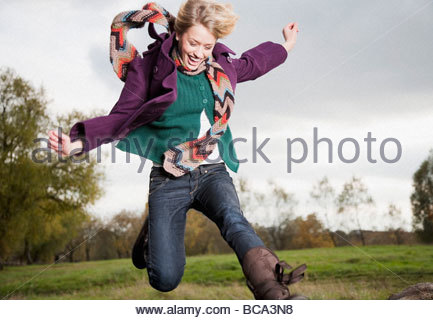 Woman jumping in mid-air in park - Stock Photo
