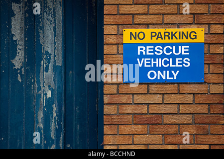 No parking rescue vehicles only sign on brick wall next to faded paint garage door Barry Wales UK - Stock Photo