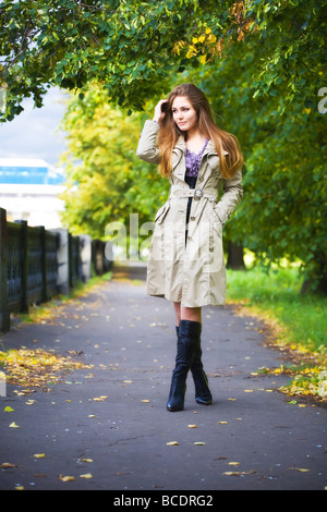 Young woman walking in autumn park - Stock Photo