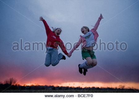 Two young girls jump atop Holmes Lake Dam in Lincoln, NE. - Stockfoto