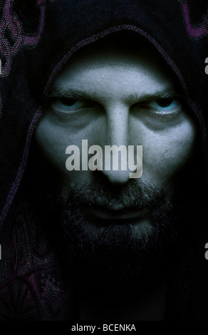 Portrait of mysterious scary man with evil look on his face - Stock Photo