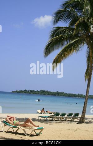 Tourist sunbathing, Bloody Bay beach, Negril, Jamaica - Stock Photo