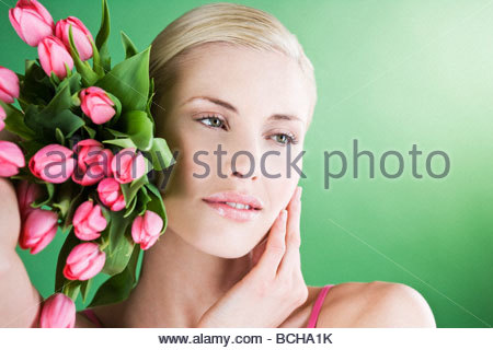 A young woman holding a bunch of pink tulips, thinking - Stock Photo