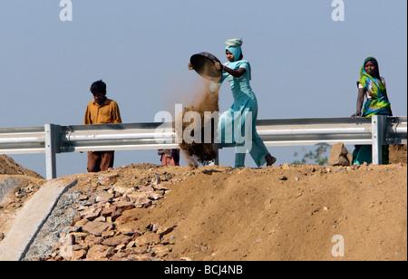 Woman in sari moves roadworks dirt Gujarat India - Stock Photo