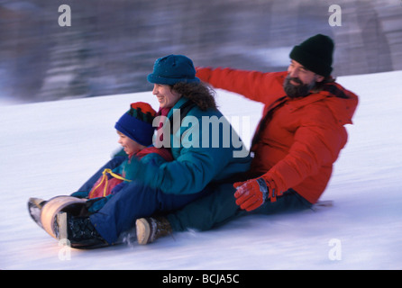 Family sledding on Tobaggan winter Alaska - Stockfoto