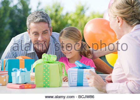 Little girl and her father looking at birthday presents - Stock Photo