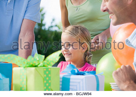Little girl and her family looking at her birthday presents - Stock Photo