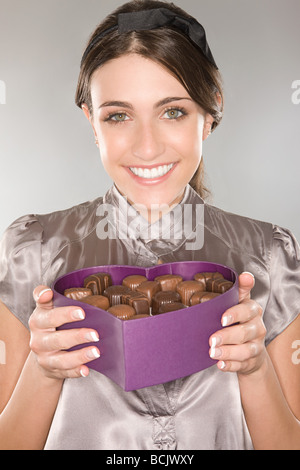 Woman holding a box of chocolates - Stock Photo