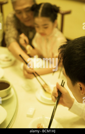 Famliy eating with chopsticks, cropped view - Stockfoto