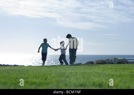 Three children running across grass, holding hands, sea in background, full length - Stock Photo