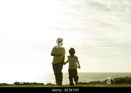Two boys running and holding hands, ocean horizon in background - Stock Photo