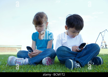 Girl and boy each using cell phones, sitting on grass, full length - Stock Photo