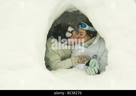 Young couple kissing in igloo, eyes closed - Stock Photo