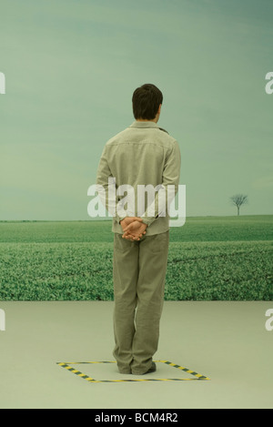 Man looking at rural scene, hands behind back, hazard tape on floor around him - Stock Photo