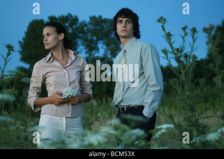 Couple standing in field, looking away, woman holding wildflowers - Stock Photo