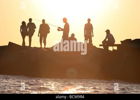 People sitting on breakwater at sunset - Stockfoto