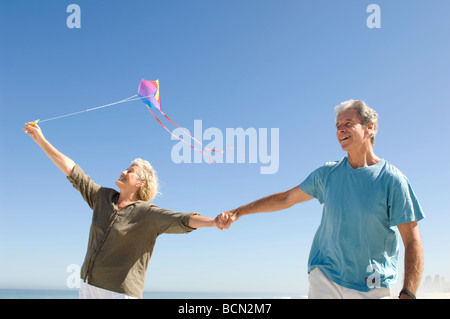 Couple running on beach holding hands and flying kite, Table View - Stock Photo