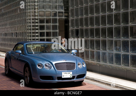 A Japanese woman speaks with a driver in a Bentley car in front of Maison Hermes building in Ginza district Tokyo - Stock Photo