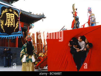Boys looking at an opera actor in full custome from underneath the stage of Henan Opera performance, Henan Province, - Stock Photo