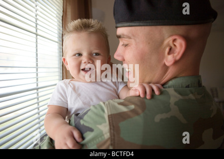 american military father coming home and greeting his infant son with a hug - Stock Photo