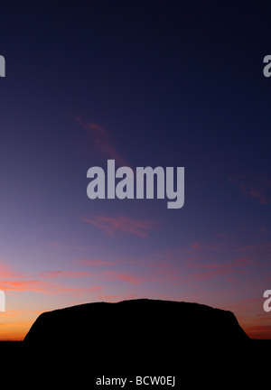 Silhouetted Uluru at twilight Central Australia - Stock Photo