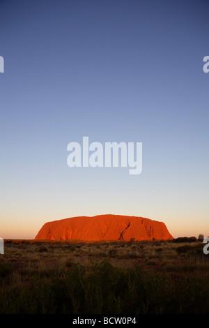 Sun setting on Uluru Central Australia - Stock Photo