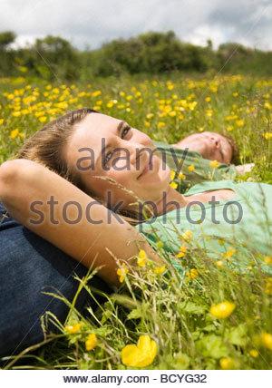 Couple Lying In Meadow - Stock Photo