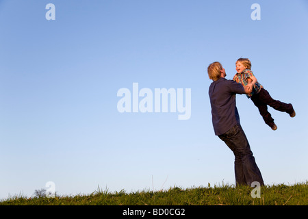 father spinning boy in his arms - Stock Photo