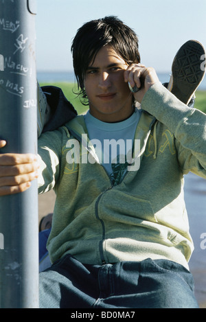 Teenage boy using cell phone, friend's feet resting on his shoulders - Stock Photo