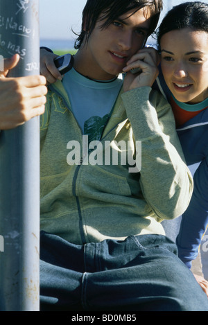 Young friends listening to cell phone together - Stock Photo