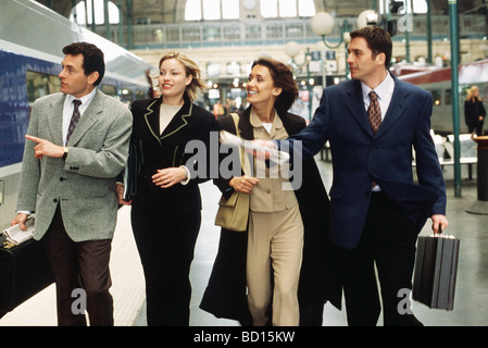 Business associates hurrying together down train platform looking for rail car - Stock Photo