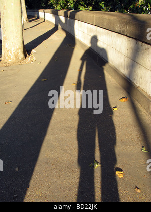 man's long shadow on pavement in city town - Stock Photo