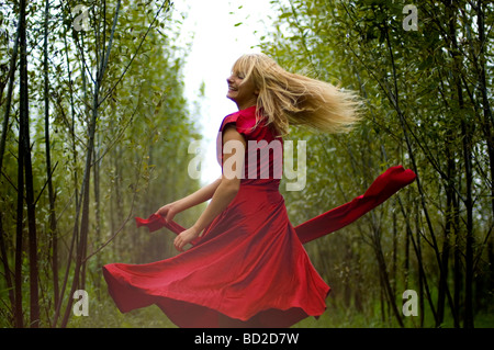 Young woman dancing in forest - Stock Photo