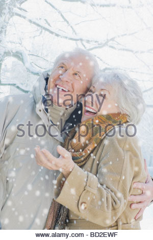 Couple smiling in snow - Stock Photo