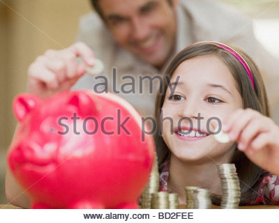 Girl putting coins in piggy bank - Stock Photo
