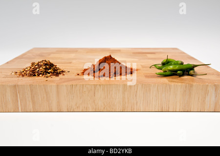 Selection of chilli types, dried, powdered and fresh, on wooden chopping board against white background - Stockfoto