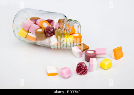 Close up of dolly mixture sweets tumbling out of glass jar against a white background - Stock Photo