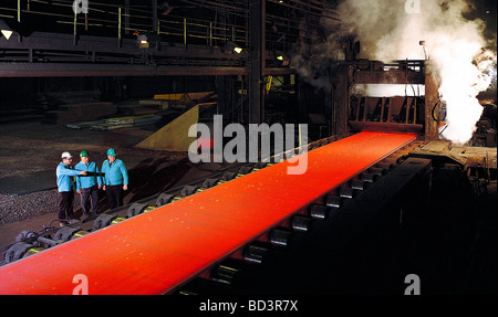 Three executives watch the rolling process of molten steel in a Pennsylvania steel mill - Stock Photo