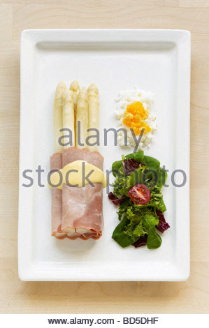 White asparagus wrapped in ham, salad leaves & chopped egg - Stock Photo