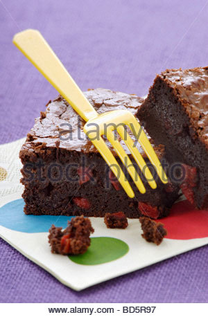 Brownie with pieces of red pepper on napkin - Stockfoto