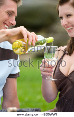 Young couple out of doors, man pouring white wine - Stockfoto