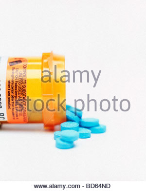 Blue Pills Spilling From a Prescription Bottle - Stock Photo