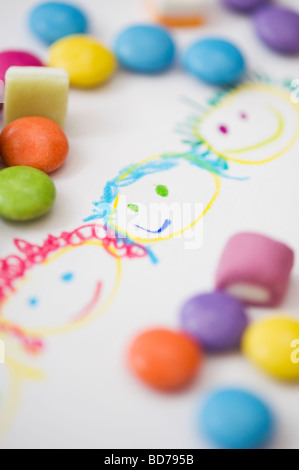 Childs coloured drawing of happy smiling faces with sweets - Stock Photo